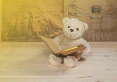 Björnleksakinnehav och läsning en bok Arkivfoto