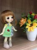 BJD et x28 adorables ; doll& x29 de joint à rotule ; position à côté du pot de fleurs truqué photographie stock libre de droits