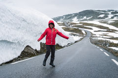 Bjorgavegen snowy road in the mountains of Norway. Bjorgavegen - Snowy road in Norway. Joyful girl on a mountain road near a wall of snow. Severe northern Royalty Free Stock Images