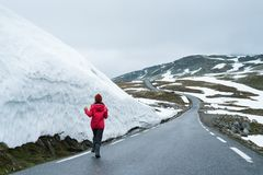 Bjorgavegen snowy road in the mountains of Norway. Bjorgavegen - Snowy road in Norway. Joyful girl is running on a mountain road near a wall of snow. Severe Stock Image