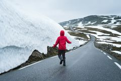 Bjorgavegen snowy road in the mountains of Norway. Snowy road in Norway. Joyful girl on a mountain road near a wall of snow. Severe northern landscape Royalty Free Stock Image