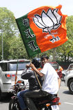 Bjp party workers in India. NEW DELHI-MAY 17: BJP supporters riding motorbikes  carrying BJP flags on the busy streets of Delhi during a roadshow after wining Stock Images