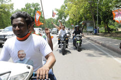 Bjp party workers in India. NEW DELHI-MAY 17: BJP supporters riding motorbikes  wearing Modi branded t-shirts during a roadshow after wining the Indian National Royalty Free Stock Image