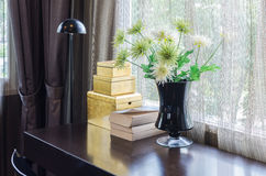 Bkack vase of flower on wooden table with black lamp Royalty Free Stock Photography