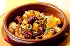 Bläckfisk med stekte potatisar i en leraplatta (mjuk fokus) Royaltyfria Foton