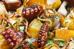 Bläckfiskgalicianstil bläckfisk som stekas med potatisar och lökar Moget frö av granatäpplet Royaltyfri Foto