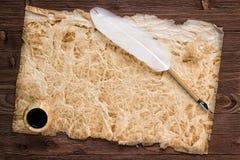 Bläckhorn och vit fjäder på en bakgrund av den tomma formen för arkivbild