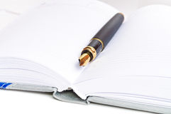 Bläckpenna och en anteckningsbok Arkivbild
