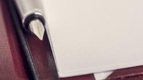 Bläckpenna som ligger i en lädermapp bredvid ett tomt stycke av papper Royaltyfri Bild