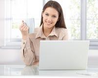 Bläddra internet för lycklig kvinna hemma arkivfoton