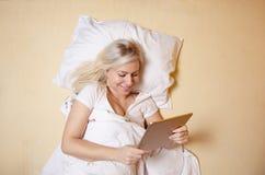 Bläddra internet i säng, härlig ung kvinna royaltyfri foto