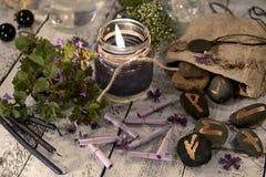 Bläddrar träffande stilleben för förmögenhet med den svarta stearinljuset, runor och önskaen Arkivbilder