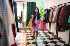 Blända kvinnlign av 30-tal som rymmer packar i det bekläda lagret arkivfoton