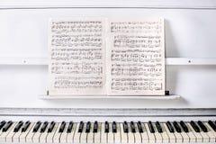 Blänka det vita härliga pianot framtill med anmärkningar på en ställning Royaltyfri Foto