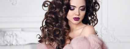 Blänka skönhetmakeup Brunetten med stil för lockigt hår bär i p royaltyfri bild