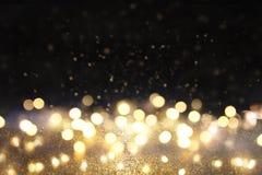 Blänka tappningljusbakgrund svart guld defocused royaltyfri foto