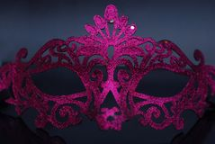 Blänker festliga purpurfärgade rosa färger för utsmyckad karnevaltappning klänningmaskeringen på mörker - blå bakgrund arkivbild