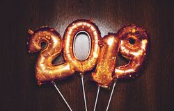 Blänker ljusa metalliska guld- ballongdiagram för nytt år 2019, jul, ballongen för det nya året med stjärnor på mörk träbakgrund royaltyfria bilder