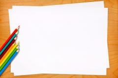 Blätter des leeren Papiers mit farbigen Bleistiften Lizenzfreie Stockbilder