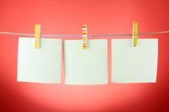 Blätter des unbelegten Papiers auf einer Kleidungzeile Lizenzfreie Stockfotos
