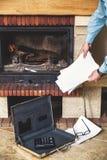 Blätter Papier in den Händen des Mannes und des Kamins Lizenzfreies Stockbild