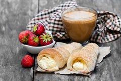 Blätterteighörner mit Schale des Cappuccinos und der Erdbeere auf Holz Lizenzfreies Stockfoto