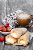 Blätterteighörner mit Schale des Cappuccinos und der Erdbeere auf Holz Lizenzfreie Stockfotografie