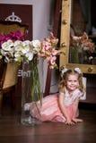 Blåögd gullig flicka i ett rosa klänningsammanträde nära en vas med orkidér och att le arkivbild