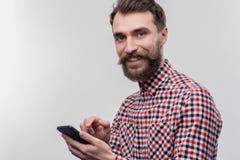 Blåögd skäggig man som tar hans svarta telefon för att kalla hans fru arkivfoto