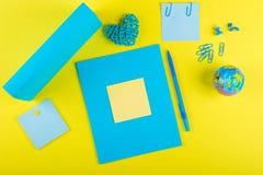 Blå åtlöje upp тетрадь och änden av läroboken för skolämnar, ett jordklot och en rottinghjärta på en gul bakgrund royaltyfria bilder