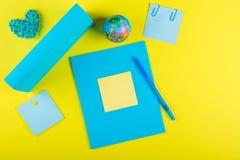 Blå åtlöje upp тетрадь och änden av läroboken för skolämnar, ett jordklot och en rottinghjärta på en gul bakgrund royaltyfria foton