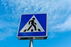 Blå övergångsställe teckenslut upp mot en molnig himmel royaltyfria foton