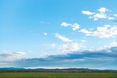 Blå aftonhimmel över vinterskördfält i vår Arkivfoto