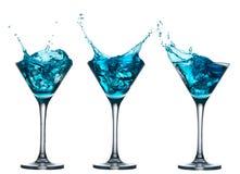 Blå alkoholcoctailuppsättning med färgstänk på vit Arkivbilder