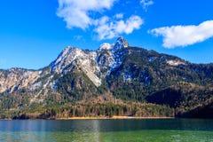 Blå Alpsee sjö i den gröna skogen och de härliga fjällängbergen bavaria fussen germany Royaltyfri Bild