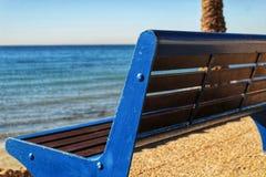 Blå bänk med havssikt på stranden arkivbild
