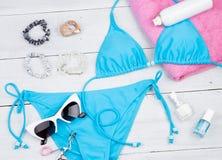 blå baddräkt, rosa handduk, skönhetsmedelmakeup, smycke och väsentlighet på det vita träskrivbordet arkivbilder