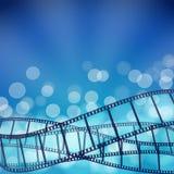 Blå bakgrund för bio med filmremsor och ljusa strålar Royaltyfri Bild