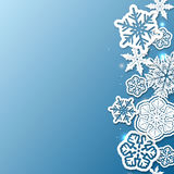 Blå bakgrund för vinter med pappers- snöflingor Arkivbilder