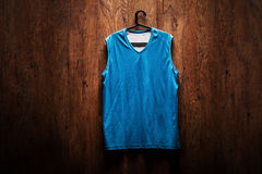 Blå basketärmlös tröja som hänger på en trävägg Arkivbild
