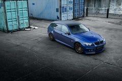 Blå bil BMW 3 serie E91 som står near behållare Arkivfoto