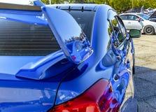 Blå bil med reflekterande målarfärg i parkeringsplats arkivbild