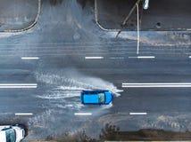 Blå bil på den våta gatan efter hällregn flyg- sikt arkivfoton