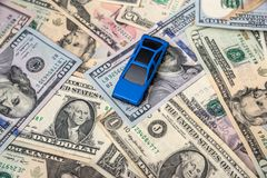 Blå bilmodell på dollar Royaltyfria Bilder
