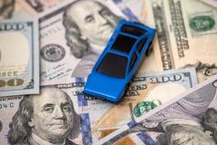 Blå bilmodell på dollar Royaltyfri Fotografi