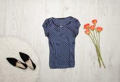 Blå blus med prickar, skor och orange rosor på en träbakgrund trendigt begrepp Royaltyfri Foto