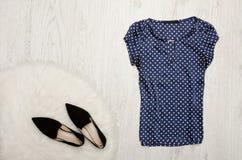 Blå blus med prickar, skor på en träbakgrund Fashi Royaltyfria Foton