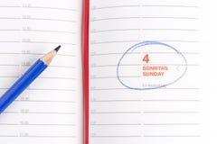 Blå blyertspenna och anteckningsbok Arkivbild