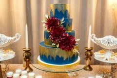 Blå bröllopstårta som dekoreras, genom att stå för blommor av den festliga tabellen med öknar, jordgubbetartleten och muffin bröl royaltyfri foto