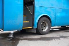 Blå buss på en station med den öppna dörren, ingen Royaltyfri Bild